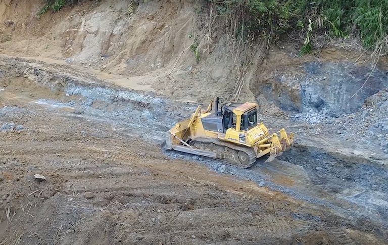 A bulldozer clears land on Woodlark. Image from Geopacific Resources via Youtube.
