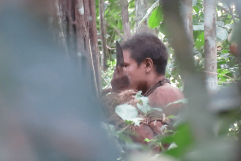 "Screenshot of the documentary film ""Ka'a Zar Ukyze Wà"" — Forest Keepers in Danger — showing a member of the Awá Guajá Awá Guajá 'uncontacted' tribe smelling a machete left in the area by outsiders, unaware he was being filmed"