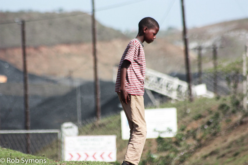 A boy playing near Tendele's washing plant: the coal mine has impacted life in the community. Image by Rob Symon via Flickr (CC BY-NC-ND 2.0)