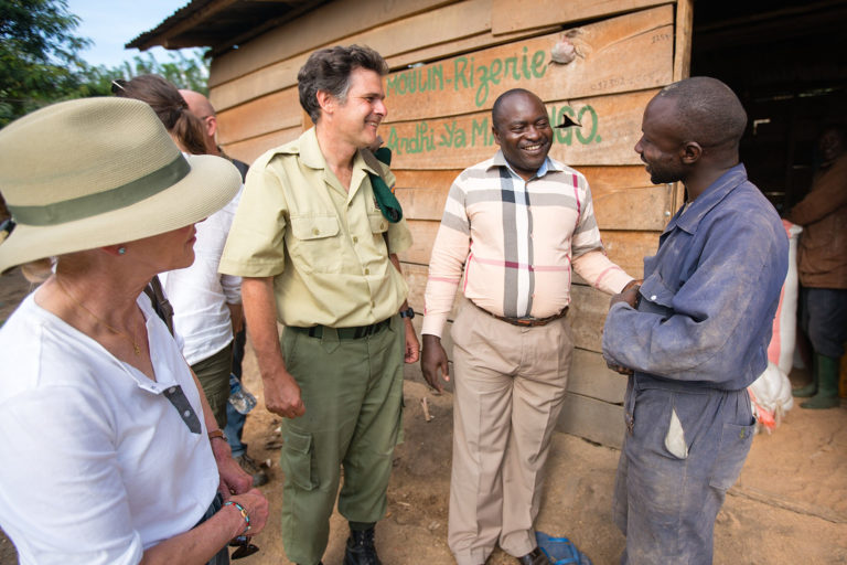 Wendy Schmidt, Virunga National Park's Director Emmanuel de Merode, and Ephrem Balole, talk with a rice mill owner. The mill uses clean energy generated by run-of-river micro hydropower stations built by The Virunga Alliance. Photo by Rian deVos, The 11th Hour Project.