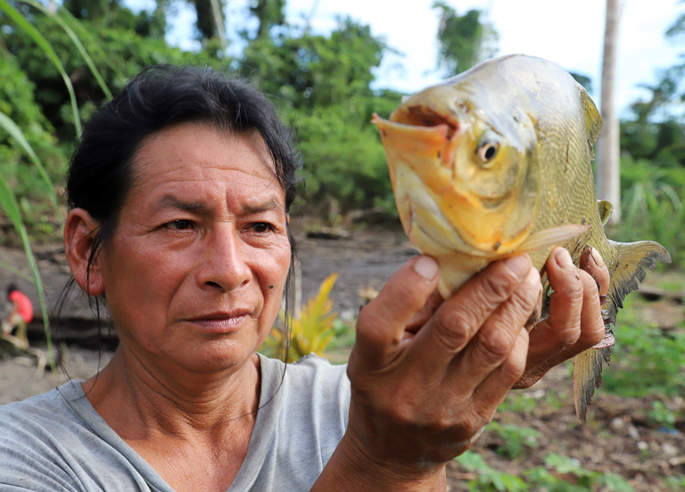 Holding a piranha pulled from the river in Wampis territory. Image by Pablo Lasansky.