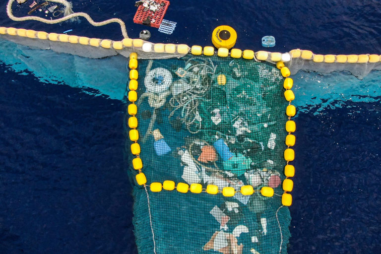 "This cleanup device, which consists of a screen attached to a floating barrier, sweeps up plastic pollution on the ocean's surface like a ""giant Pac-man."" Photo credit: the Ocean Cleanup"