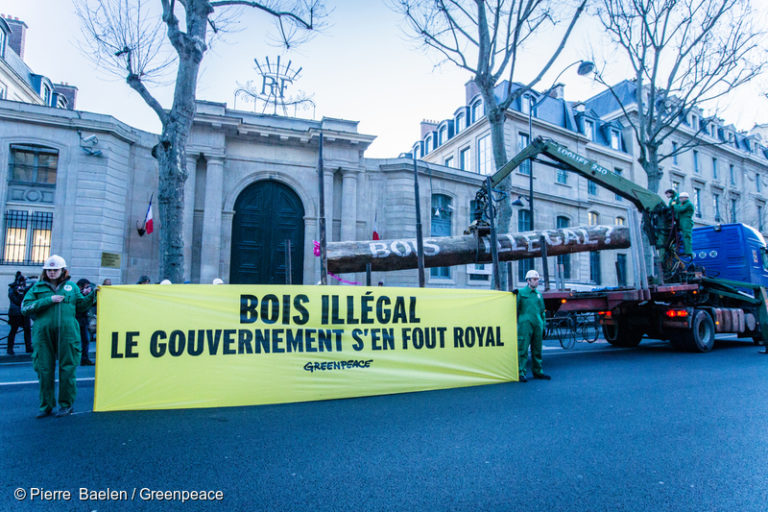 "Greenpeace activists deliver a tropical timber log to the front door of the Ministry of Ecology in France. Activists, wearing uniforms of ""Brigade de Vérification de Bois"" (BVB) hold banners reading ""Illegal timber: the government doesn't care"" and ""Illegal timber: two years of inaction."" Photo © Pierre Baelen / Greenpeace."