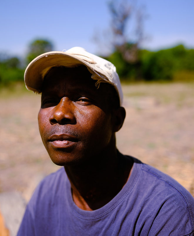 Headshot of forestry agent Malam Djassi wearing white baseball cap and blue t-shirt. Image by Ricci Shryock for Mongabay.
