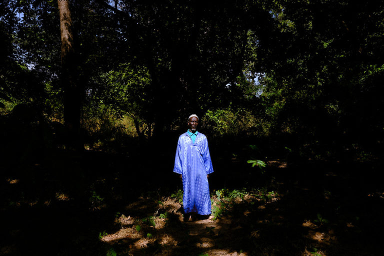 Village head Talibo Coté in a light blue kaftan in a forest near his hometown, Djendo. Image by Ricci Shryock for Mongabay