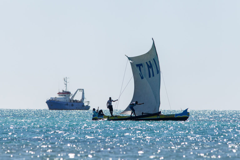 Marine conservation efforts in Madagascar - and a growing number of coastal states - are increasingly focusing on the securing the rights of traditional fishers to protect their seas from industrial trawling. For example, this photo shows Vezo traditional fishermen in southwest Madagascar sailing past a deep water shrimp trawler. While traditional fishermen have fished these waters for centuries, they have no formal claim to them. About 150 foreign industrial fishing vessels are licensed to fish within the waters of Madagascar. Photo © Garth Cripps / Blue Ventures.