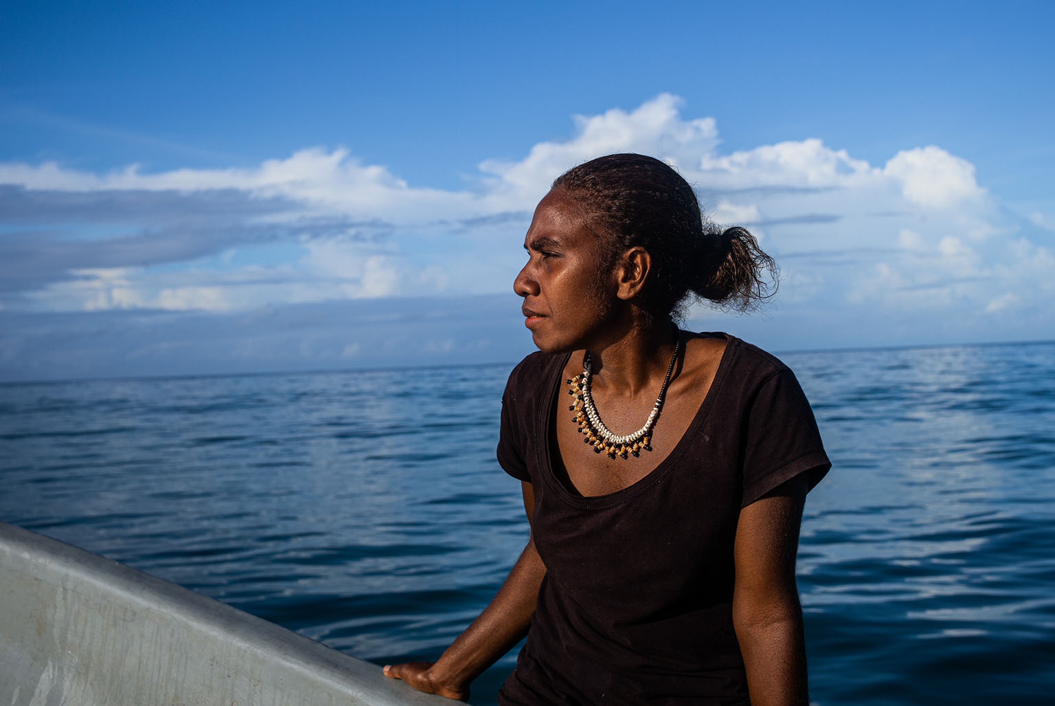 This image from the Solomon Islands, is of a young woman returning to her village by boat from Malaita Island, after a long trip to gather supplies and food. Photo credit: Daniel Lin