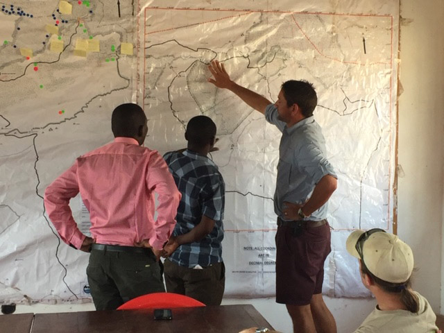 Conservationists looking at a map of Nsumbu National Park, Zambia. Photo credit: Rodger Schlickeisen.