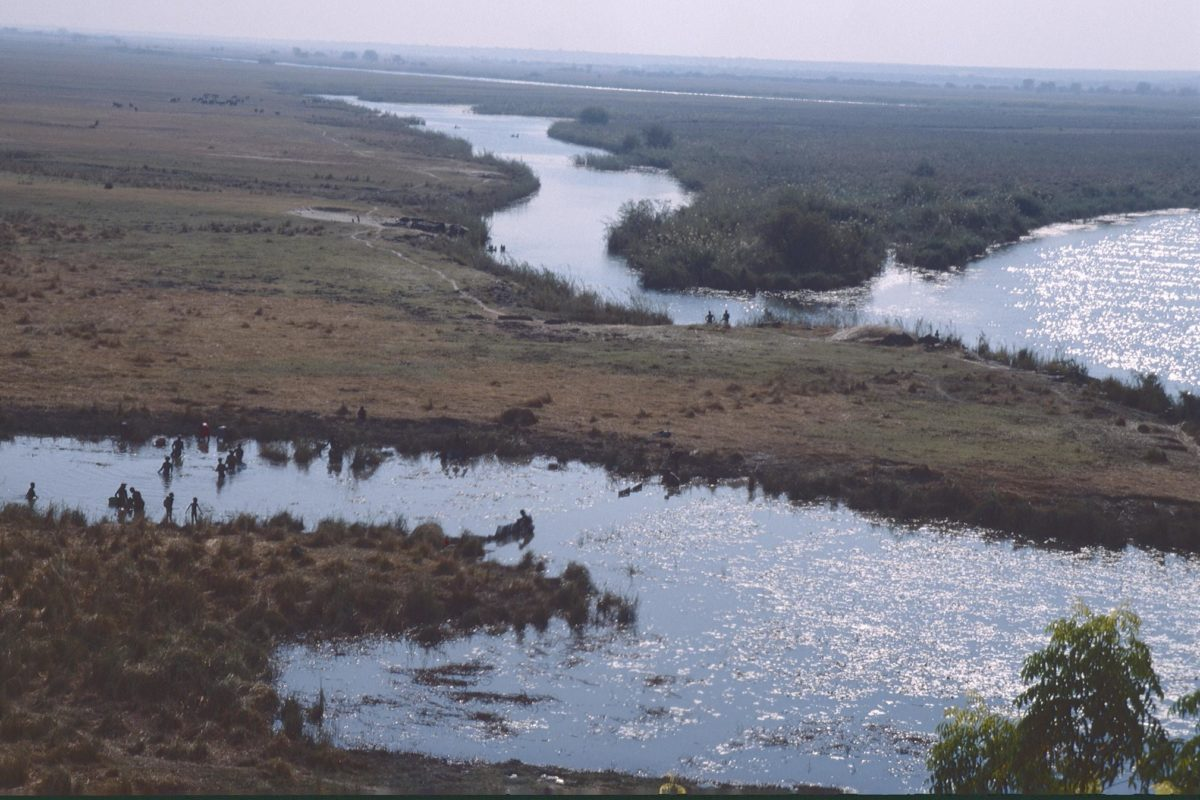 Aerial shot of river near Rundu, Namibia with small figures on the banks. Image by Patrik M. Loeff via Flickr (CC BY-NC-ND 2.0)