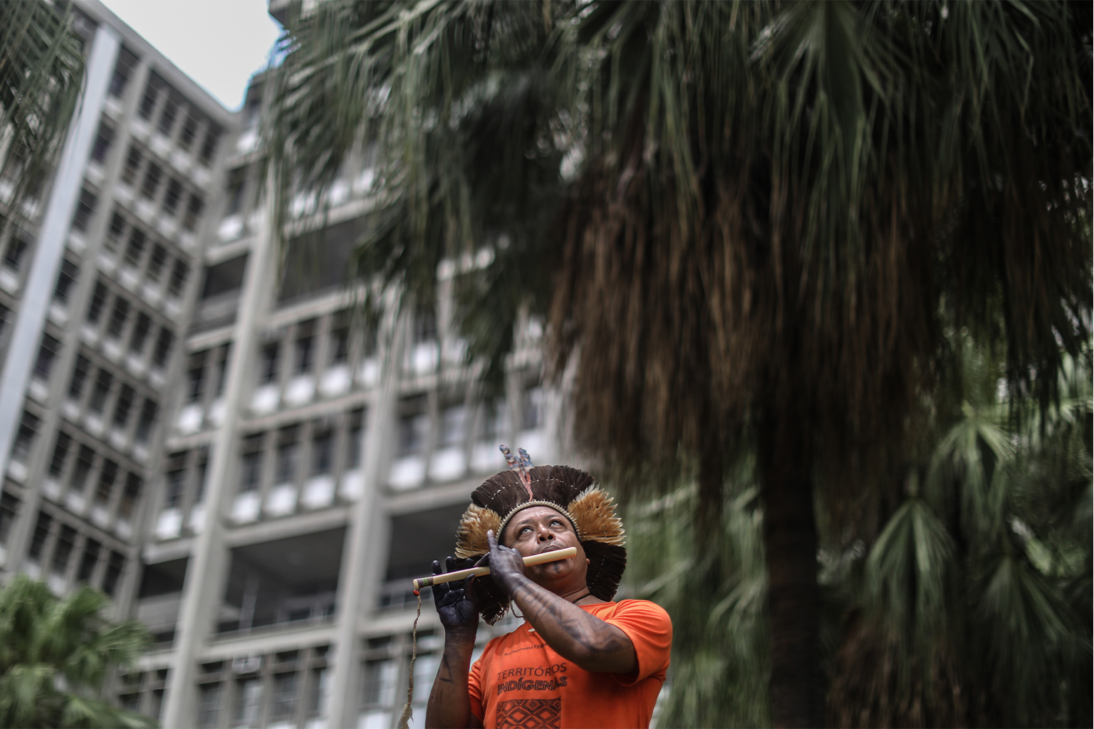 A man wearing Indigenous headwear stands and plays an instrument in front of a building and trees.