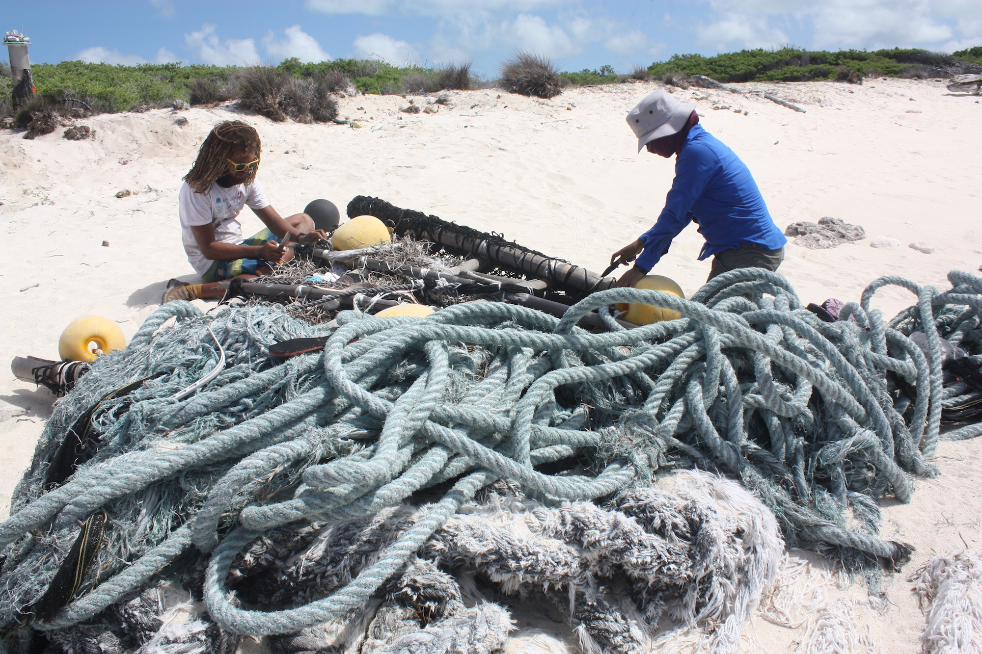 Jeremy Raguain, left, and Kalsey Belle, who took part in the 2019 cleaning drive on Aldabra, taking apart a beached FAD. Image Courtesy of April Burt.