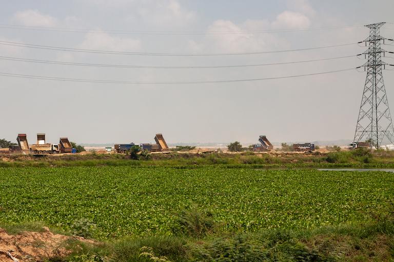 A row of dump-trucks deposit infill along the shore of Boeung Tamok. Image by Gerald Flynn for Mongabay.