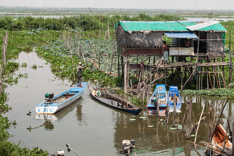 A farmer's house is visited by a boatman in the rapidly shrinking Boeung Tamok. Image by Gerald Flynn for Mongabay.