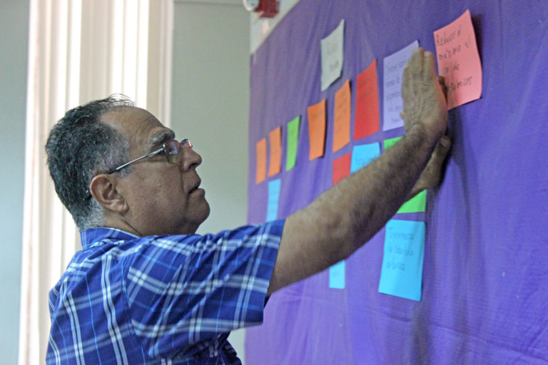 A participant posting to a sticky wall at a Behavior Centered Design (BCD) training workshop hosted by Rare's BE.Center in Colombia. May 2019. Photo credit: Rare.