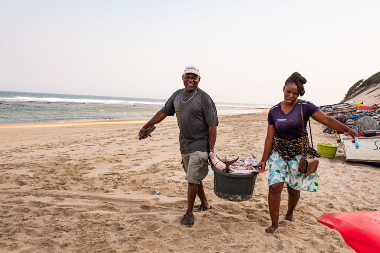 """Henriqueta Watevão Vamusse (right) with Zefanias """"Jeff"""" Joel Zango (left) buying fish (mostly King Mackerel (Scomberomorus commerson), locally known as couta or saw fish) on the beach from local fishermen. Závora, Mozambique. October 2018. Photo credit: Jason Houston for Rare."""
