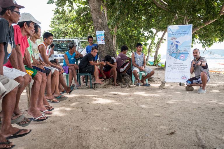 Japy Toledo Silapan, Program Manager, does an initial community consultation explaining Rare's coastal fisheries program named Fish Forever. Mambungalon, Philippines. Commission for Rare. September 2016. Photo credit: Jason Houston for Rare.