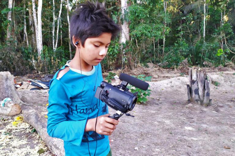 Cajubi, membre de l'Uru-eu-wau-wau, apprend à utiliser une caméra vidéo alors que sa communauté reste en confinement.