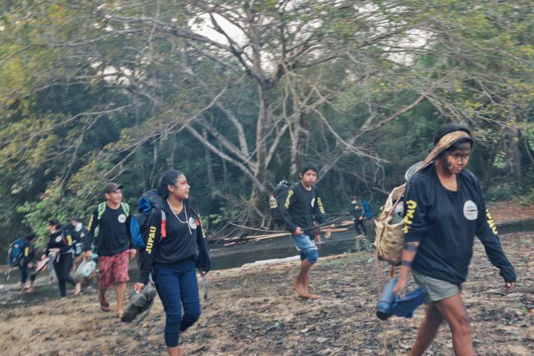 Les membres de l'équipe de surveillance Uru-eu-wau-wau se lancent dans un voyage à travers leur forêt indigène, portant leurs effets personnels sur leur dos. Image reproduite avec l'aimable autorisation de l'Uru-eu-wau-wau