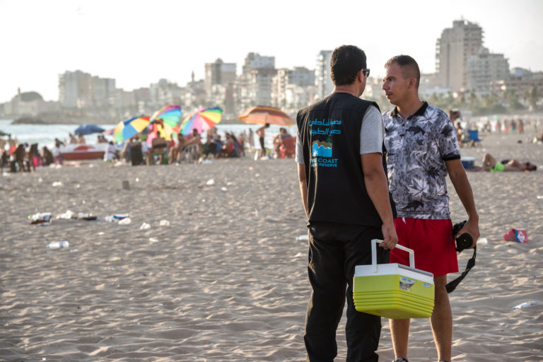 Tyre,-Lebanon,-July-2021.-Tyre-Coast-Nature-Reserve-Vice-Director,-Hassan-Hamza-waits-on-Tyre-Public-Beach-with-85-Loggerhead-turtle-hatchings-in-a-picnic-box