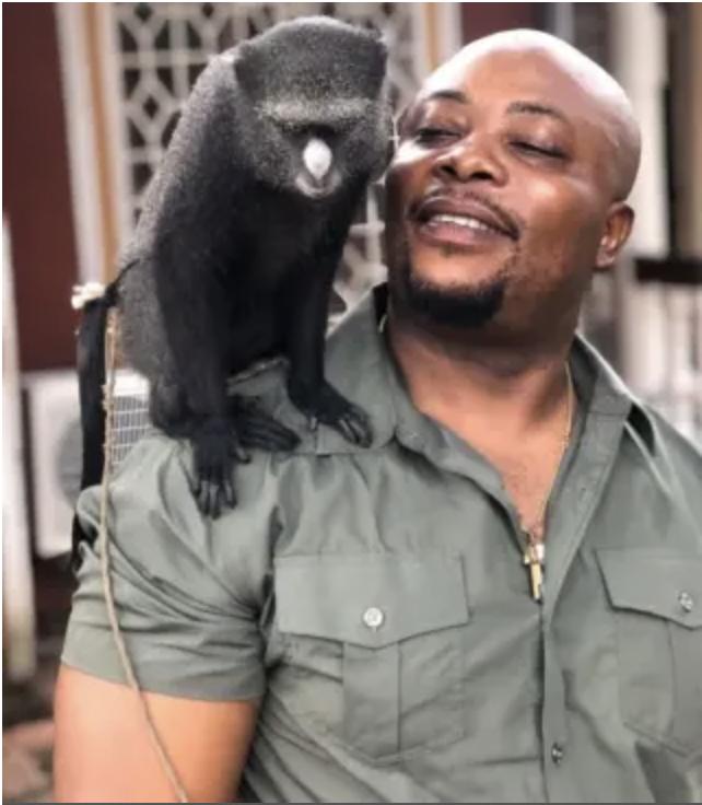 Adams Cassinga with a putty-nosed monkey. Image courtesy Adams Cassinga.
