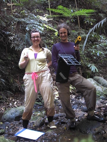 Betsy Roznik (right), armed with a RECCO tracking device to locate tagged frogs, pauses in the forest with a colleague. Photo by Betsy Roznik.