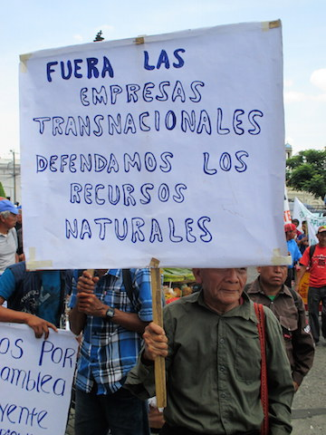 "A protester at the May 20 demonstration in Guatemala City carries a sign reading ""Out With Transnational Corporations; Let's Defend Our Natural Resources."" Photo by Sandra Cuffe."