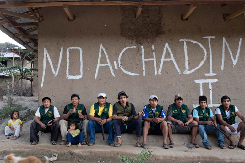 "The patrolmen of the Tupen Grande ronda pose in their uniforms beneath graffiti that reads ""No to Chadin 2."" Cesar Chavez is fourth from left. Photo credit: Danielle Villasana."