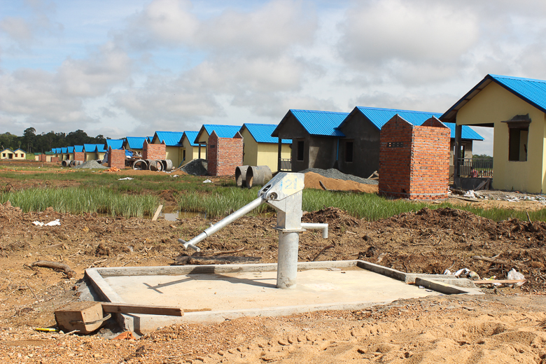 Houses under construction at the resettlement site for the Kbal Romeas commune, including a new hand water pump. The Cambodian government is relocating some 850 families from six villages that will be flooded by the Lower Sesan 2 dam. Photo credit: Anonymous.