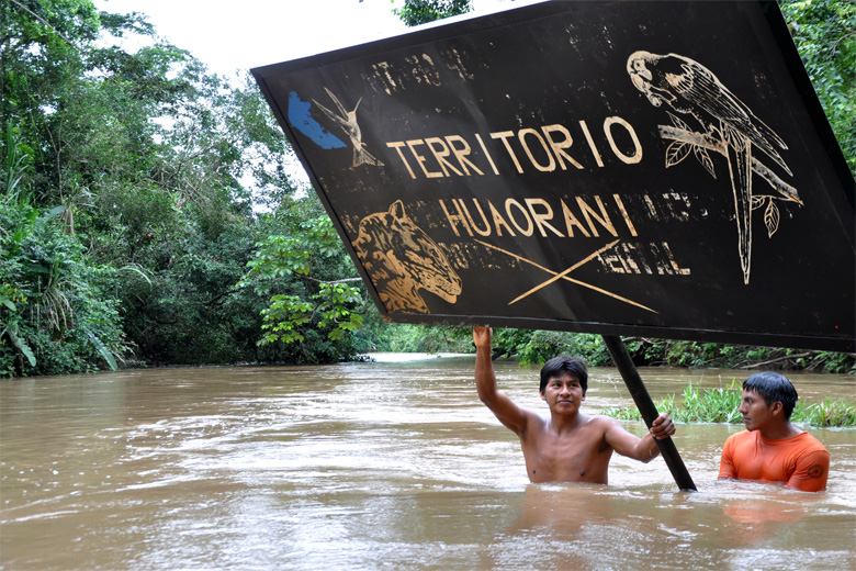 """Waorani Indians raise a sign that says """"Waorani Territory"""" in an official photo by the Ecuadorian government. Photo credit: MJDHC - Minister of Justice and Human Rights in Ecuador."""