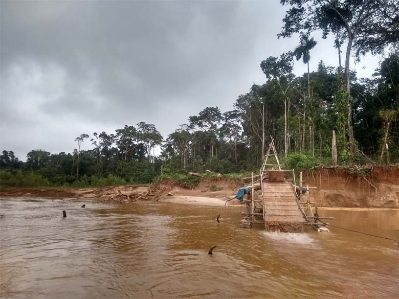 """A balsa gringa, a type of mining raft, in action near APAYLOM. The raft dumps river water over the ramp in the back, which is lined with carpet. The riffles on the back agitate the water, allowing the lighter materials to run off while the gold and other heavy materials soak into the carpet."""" Photo Credit: Saul Elbein"""