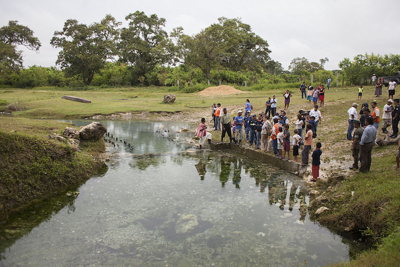 Sayaxché residents gather by a stream during a visit in July by Guatemalan government and UN officials to communities affected by the mass fish die-off in June. Photo by CONRED Guatemala.