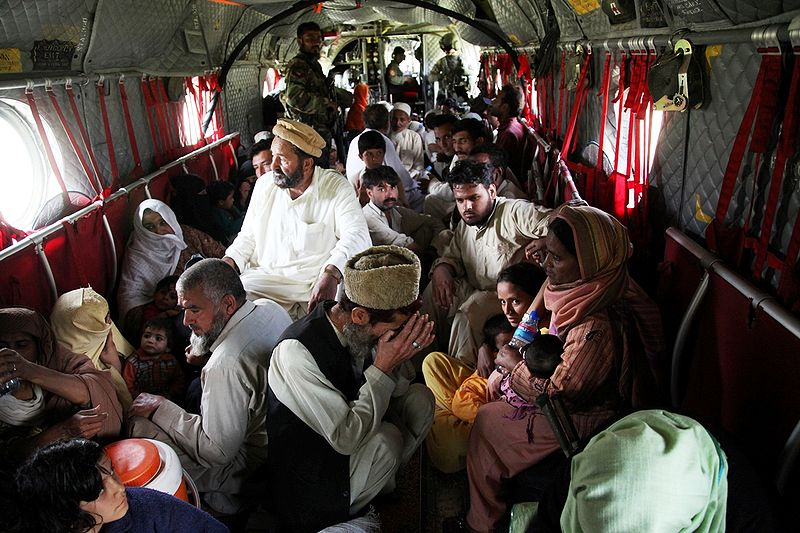 "Floods in Pakistan August 4, 2010. Pakistanis rescued from one of their nation's most devastating floods on record sit on the floor of a U.S. Army CH-47 Chinook helicopter during disaster relief evacuation mission from Khyber Pakhtunkhwa. ""What we are asking for is a fair, legally binding and truly transformational agreement by all the nations on earth,"" said Cardinal Oswald Gracias, President of the Federation of Asian Bishops' Conferences and the Archbishop of Bombay, India. Photo by Horace Murray courtesy of U.S. Army"