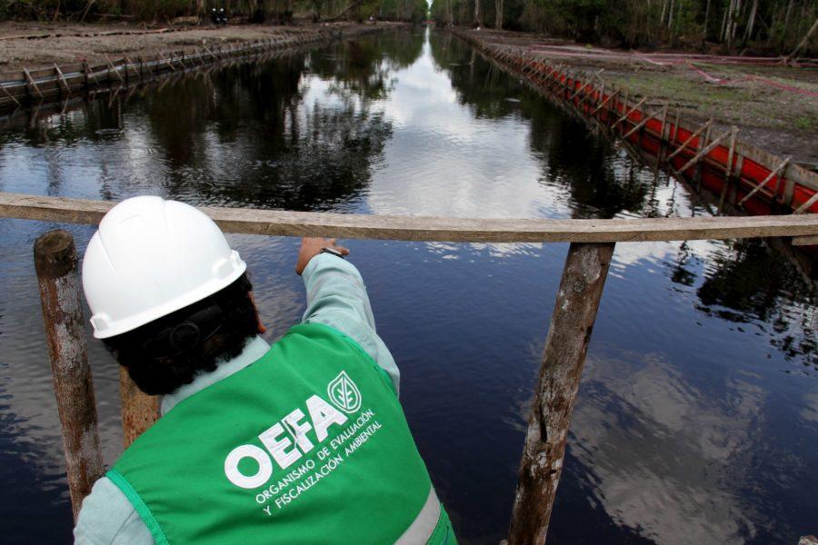 Un funcionario de la OEFA revisa el estado de un río donde hubo contaminación petrolera. Foto cortesía de OEFA.