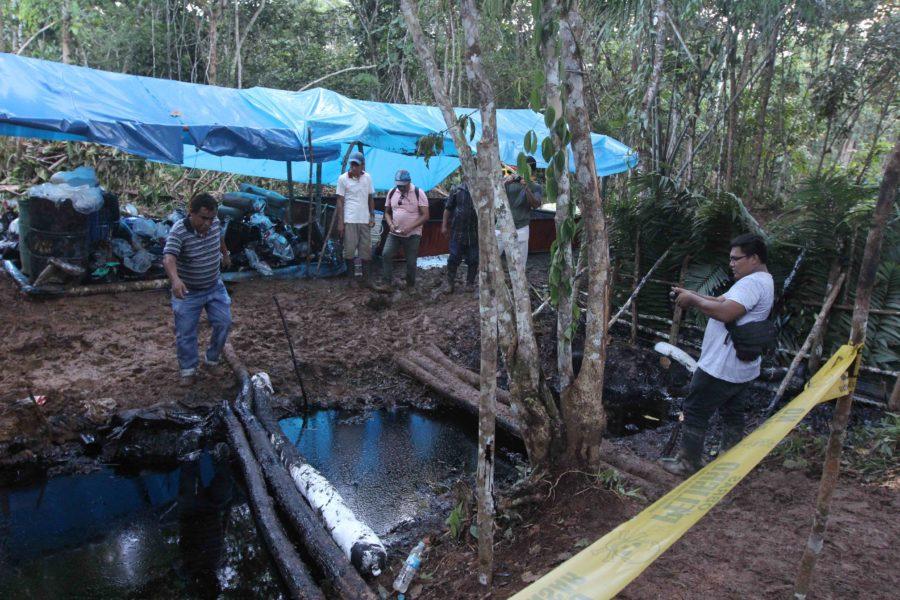 Miembros del Frente de Defensa del Marañón observan parte de la quebrada donde se ha contenido el derrame de petróleo en Barranca. Foto de Barbara Fraser.