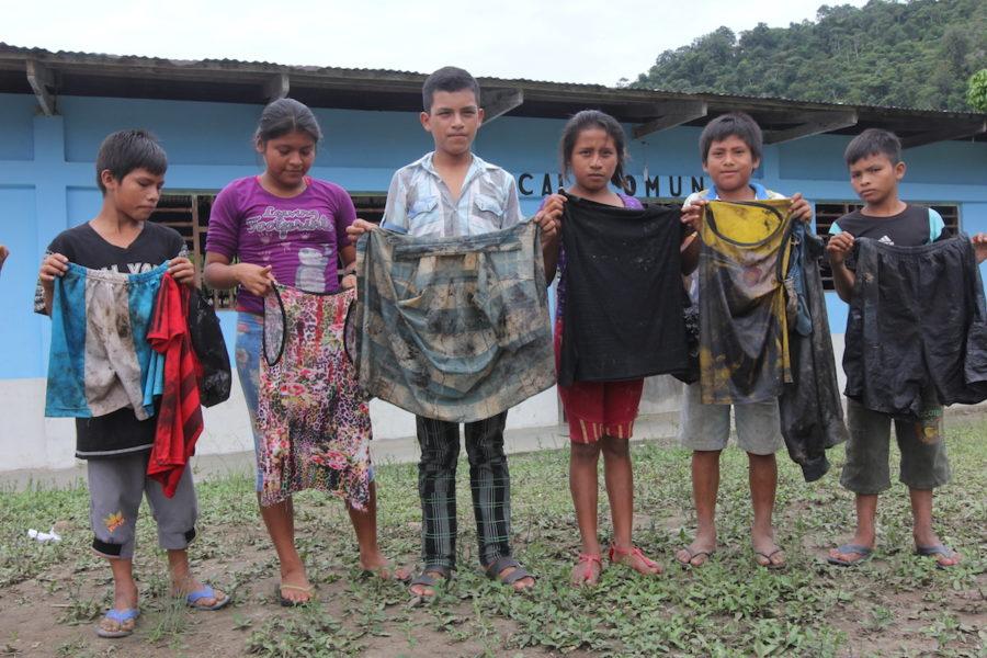 Niños en Nazaret, un pueblo en la confluencia del los ríos Chiriaco y Marañón al norte de Perú, muestran la ropa que llevaban cuando sacaban petróleo del río Chiriaco después del derrame del oleoducto. Foto de Barbara Fraser.