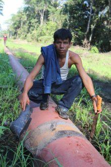 Gilter Yuharima Tapuyima, presidente de la comunidad de Nueva Alianza, indica un lugar en el oleoducto Nor Peruano donde una funda de goma protectora se desprendió, dejando al descubierto óxido en una unión de soldadura. Foto de Barbara Fraser.