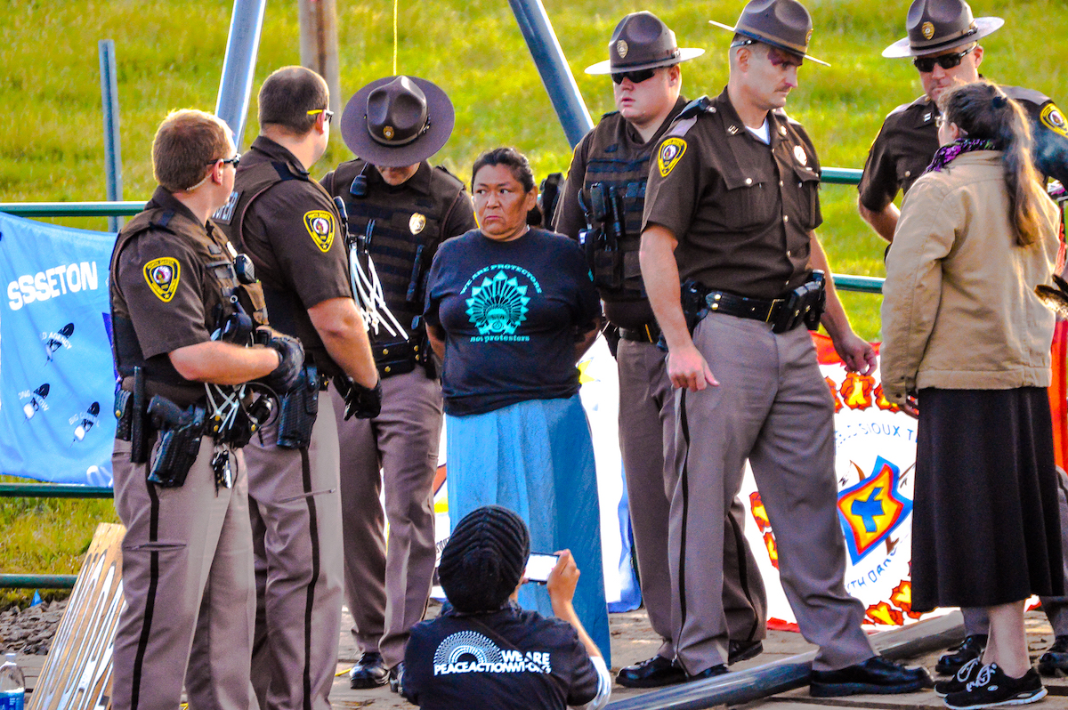 North Dakota State Troopers take an oppenent of the Dakota Access pipeline into custody in mid August, 2016. Photo by Rob Wilson for Bold Alliance
