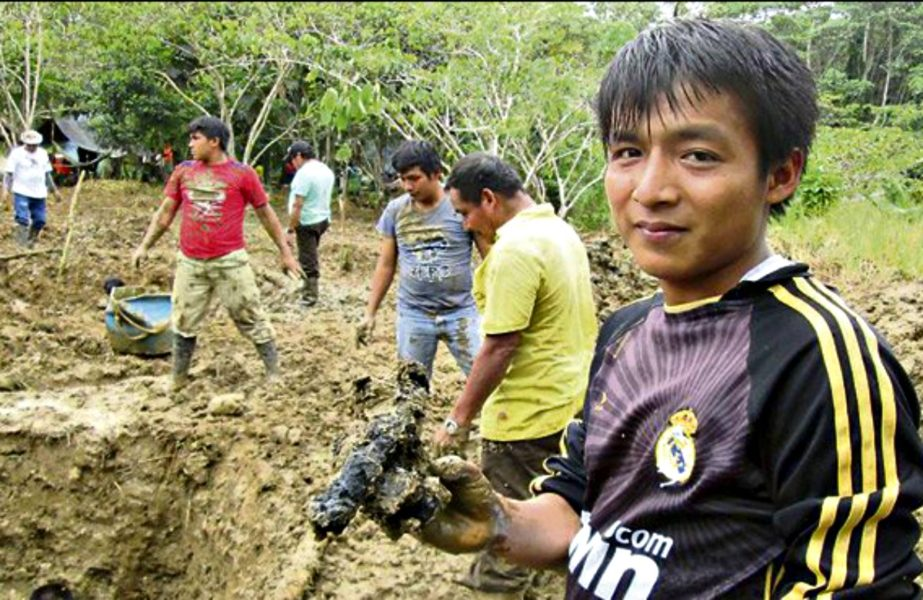 Indígena ashuar sosteniendo una masa de tierra con petróleo seco que demuestra el abandono de los pasivos ambientales. Fotografía de archivo/La República.