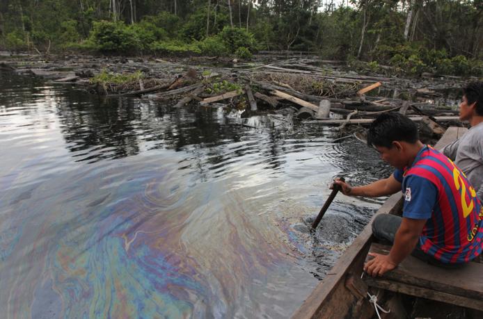 Comunero de Cuninico remueve restos de petróleo en el canal de flotación del oleoducto, dos días después que los inspectores del gobierno declararan la limpieza terminada. Foto: Copyright © Barbara Fraser.