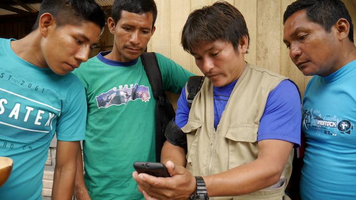 Los monitores ambientales indígenas de cuatro ríos examinan un teléfono inteligente. Foto: Dan Collyns.