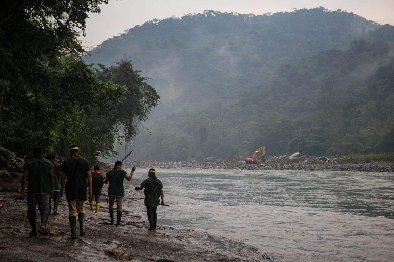 Miembros de la comunidad indígena Cofán de Sinangoe camina a orillas del río Aguarico, mientras al fondo se ve una retroexcavadora removiendo tierra. Foto: Jerónimo Zuñiga/Amazon Frontlines