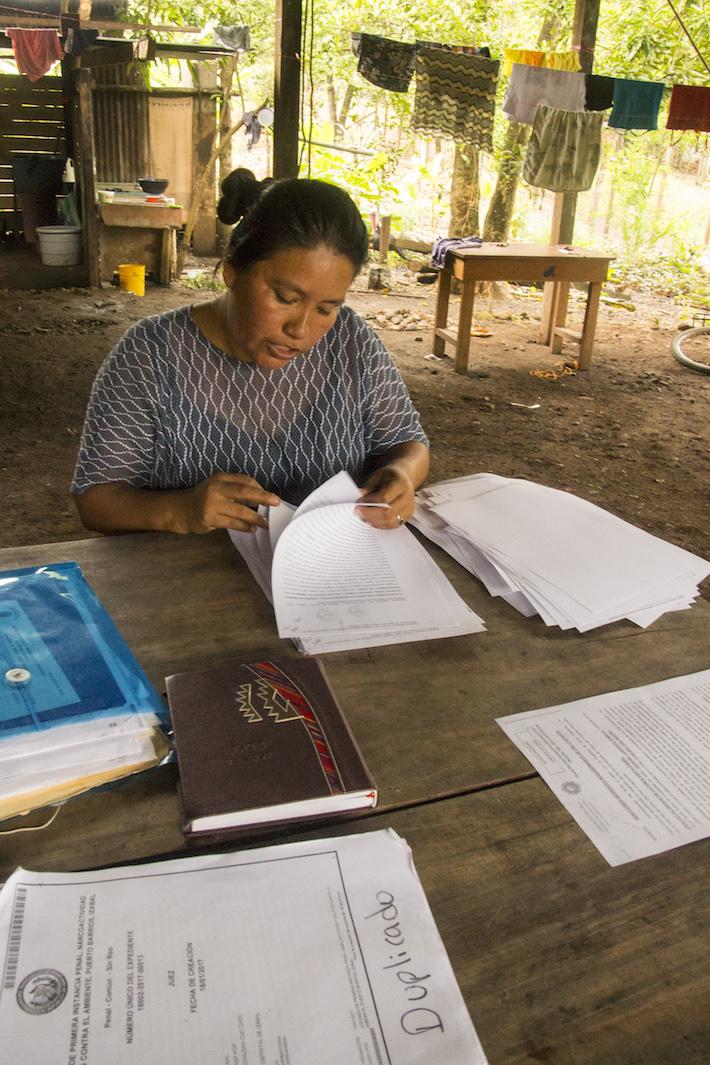 La defensora Maya Q'eqchi' MaríaCuc Choc mostra los documentos relativos a las denuncias puestas a las diferentes empresas y el acto de propiedad de sus tierras. Foto: Jessica Guifarro.