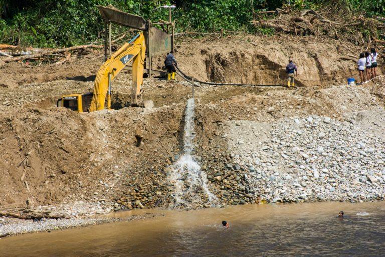 En esta imagen se aprecia como el agua usada por la minería vuelve al río, mientras niños de la comunidad Shuar nadan en él. Foto: Carlso Medina.