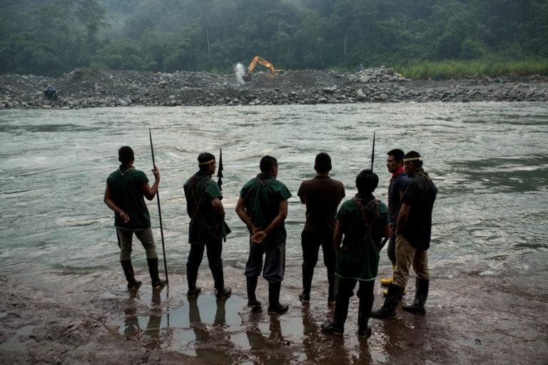 Miembros de la comunidad indígena Cofán de Sinangoe caminan a orillas del río Aguarico, mientras al fondo se ve una retroexcavadora removiendo tierra. Foto: Jerónimo Zuñiga/Amazon Frontlines