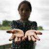 Derrame de petróleo. Las manos de una niña indígena están manchadas por el petróleo después de jugar a lo largo de las orillas del río cerca de la comunidad de San Pedro de Río Coca, Sucumbíos, Amazonía ecuatoriana, el 18 de abril de 2020. Foto: Telmo Ibarburu.