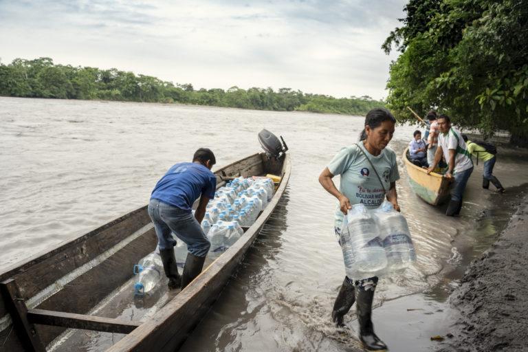 Derrame de petróleo. Comuneros llevan agua envasada a su comunidad a raíz del derrame de petróleo que afecta a su río y territorio, Sucumbíos, Amazonía ecuatoriana, el 18 de abril de 2020. Foto: Telmo Ibarburu
