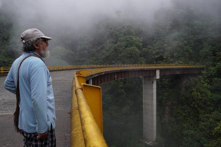 El puente en el que se encuentra Édgar Torres se estrella directamente con la montaña donde inicia la Reserva Forestal Protectora de la Cuenca Alta del Río Mocoa. Foto: María Fernanda Lizcano.