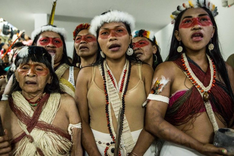 Las Waorani cantan antes de entrar en la sala de audiencia para la lectura de la sentencia waorani en el tribunal provincial en Pastaza, en la Amazonía ecuatoriana (2019). Foto: Mitch Anderson, Amazon Frontlines.