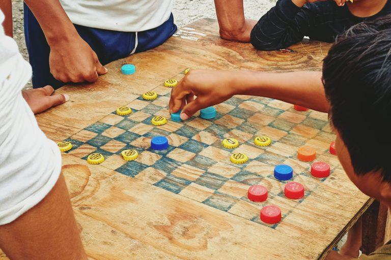 Por las noches, en medio del paro en la vía, algunos habitantes de El Edén juegan naipes o damas, por las tardes juegan ecuavoley —variante ecuatoriana del voleibol—. Foto: Diego Cazar Baquero.