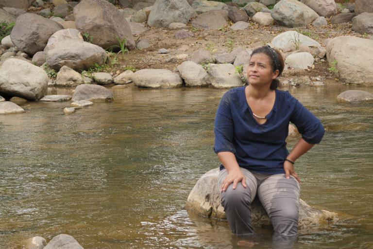 Juana Zúniga se asienta en el río Guapinol, en el pueblo de Guapinol, ubicado en el valle del Bajo Aguán en el norte de Honduras, el 4 de julio de 2021. Juana Zúniga es miembro de la comunidad Guapinol y del Comité Municipal de Tocoa, Colón por la defensa de los recursos naturales. Foto: Global Witness / María Aguilar / Iolany Pérez.
